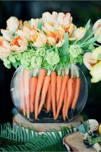 Γυάλινο βάζο με καρότα και λουλούδια.
